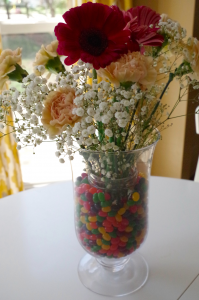 Flowers in a vase filled with jelly beans