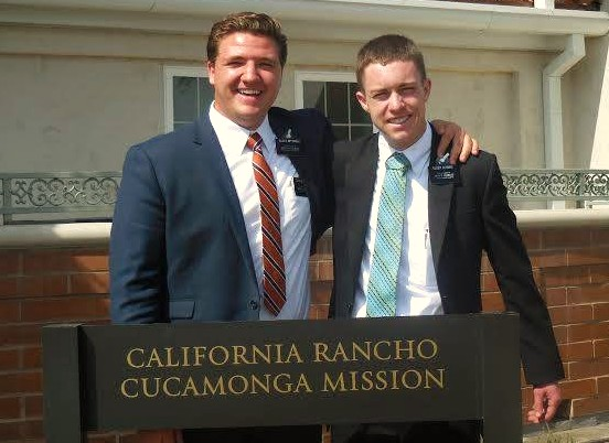 Mormon Missionary companions standing by mission sign.