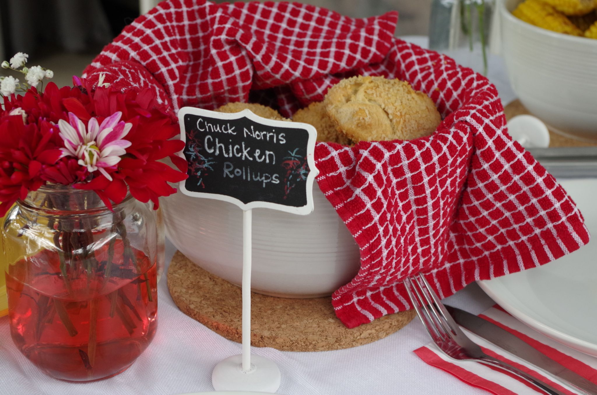 White Chalkboard food sign, red flowers, and bowl of chicken rollups with red and white checked napkin