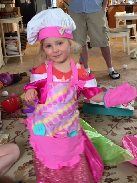 Little girl wearing an apron over a princess dress, complete with chef hat and oven mitt. She is ready to help with family mealtime.