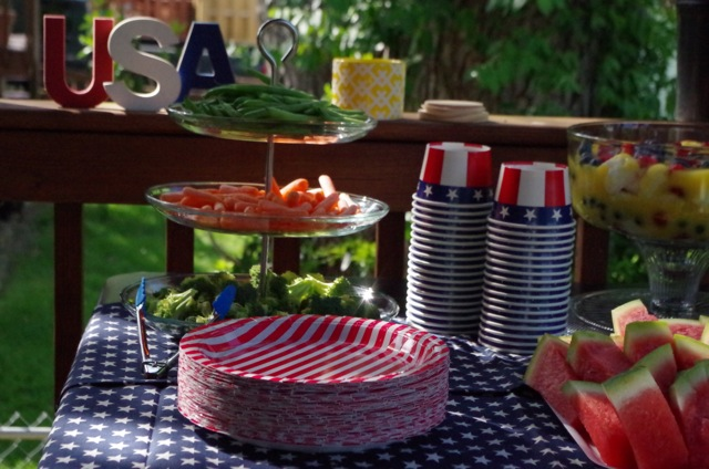 Patriotic cups and plates on a blue and white starred table cloth.