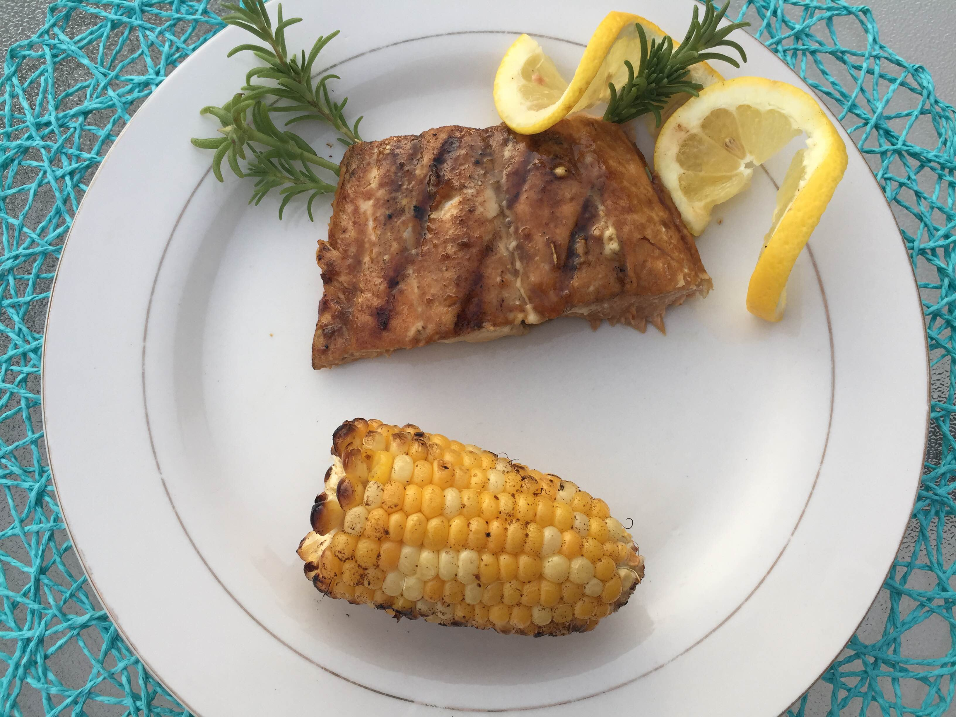 barbecued salmon on a white plate, with lemon slices and herbs