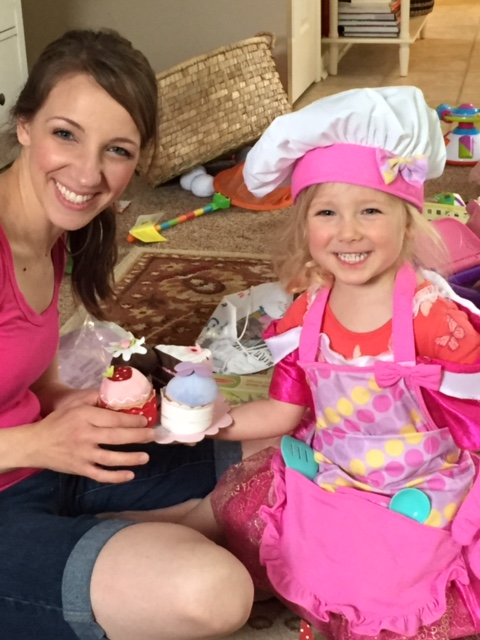 Little girl and her mom play family mealtime with pretend baked goods.