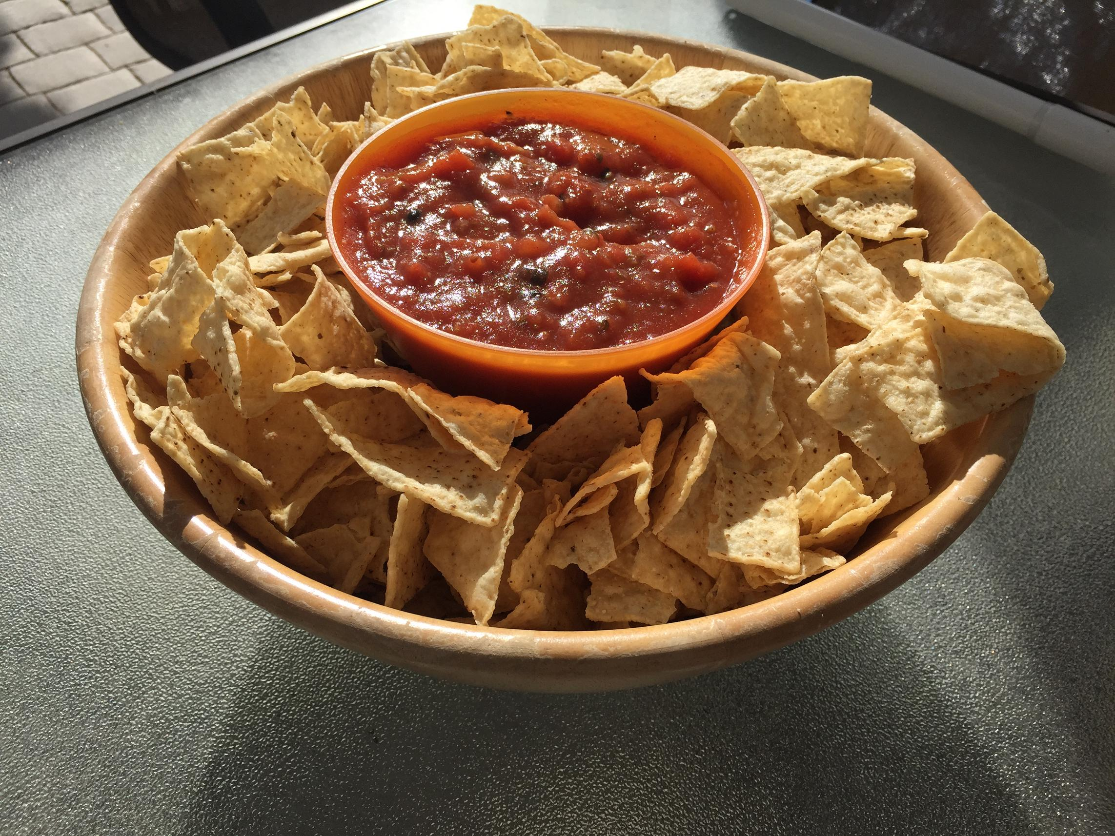 tortilla chips and salsa served in a wooden bowl
