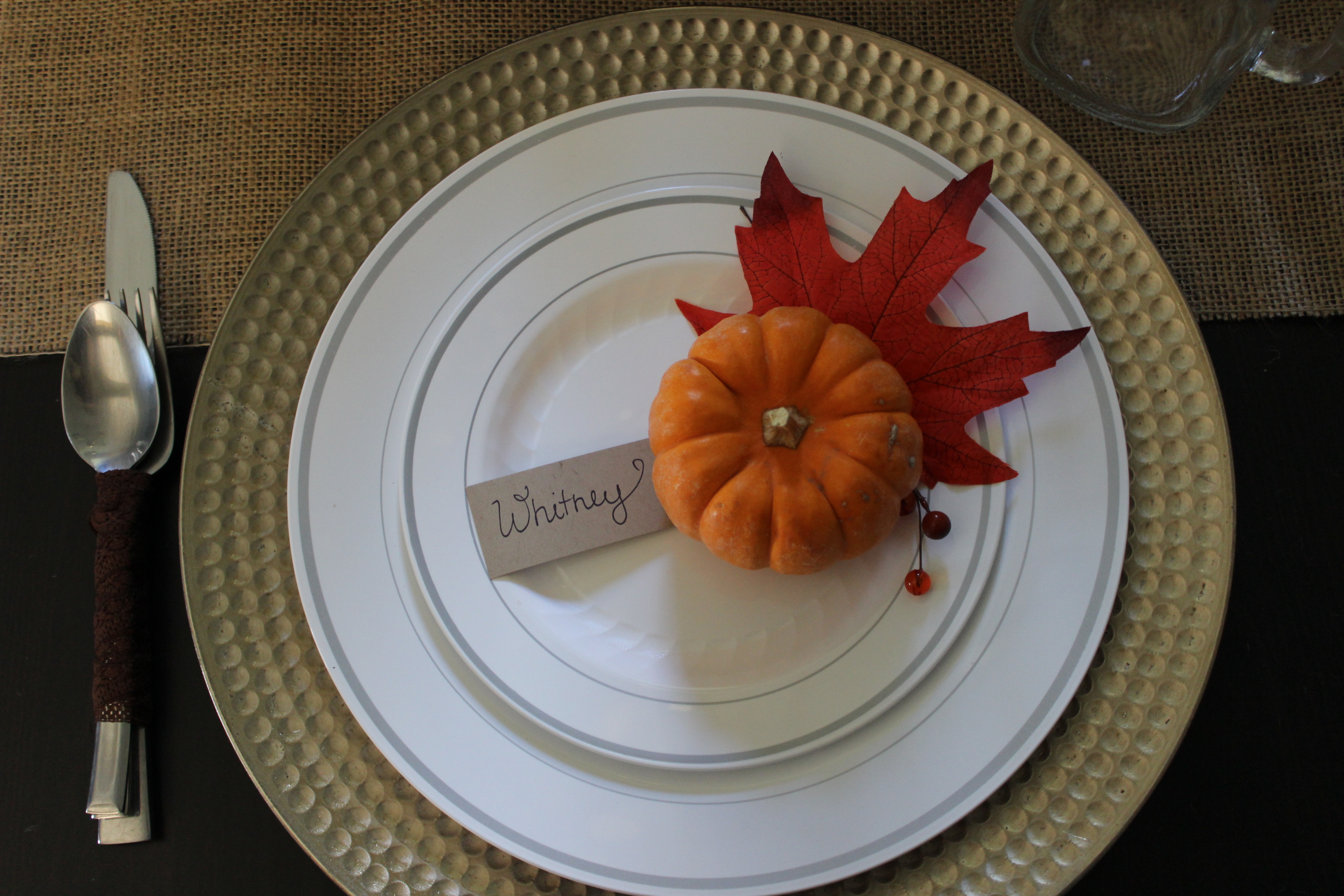 Thanksgiving table decor can incluse miniture pumpkins and silk fall leaves