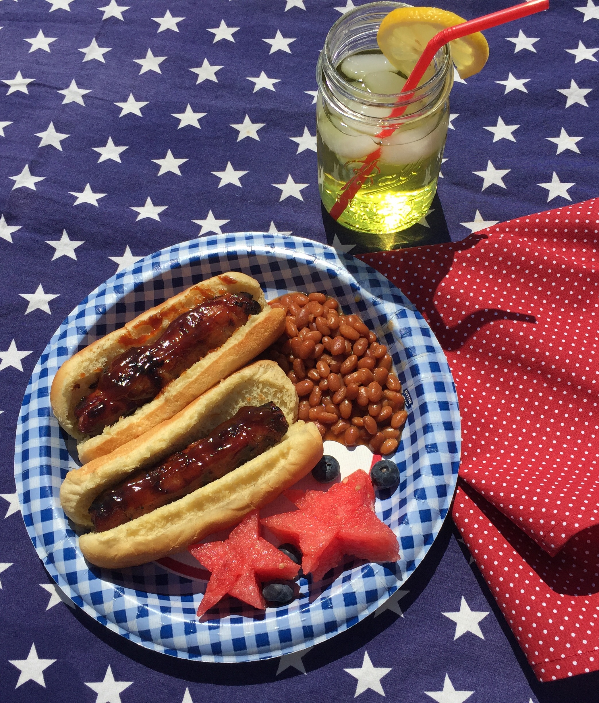 Bacaon wrapped hot dogs in barbecue sauce, on a blue checked pate with backed beans and watermelon